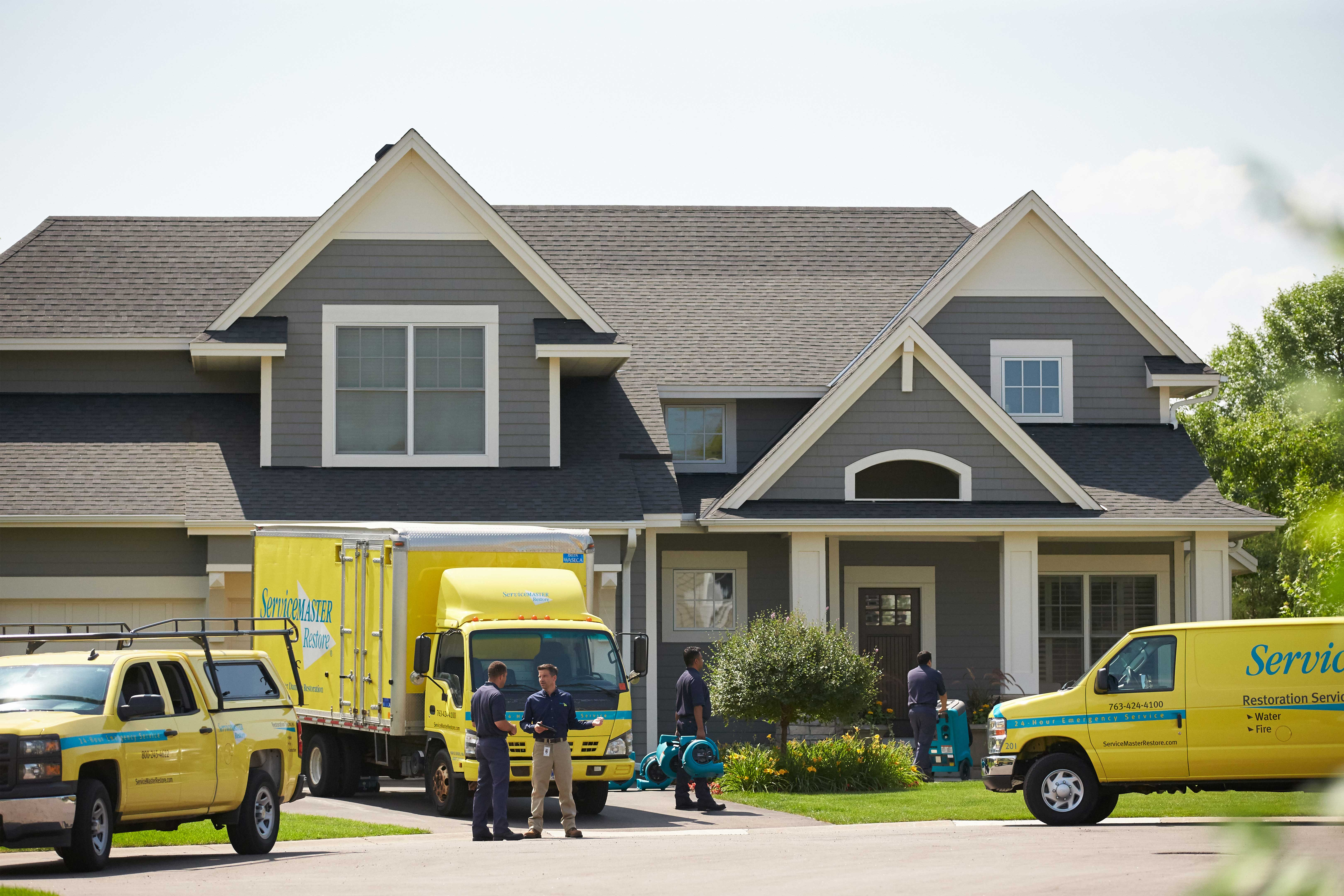 image of servicemaster vehicles at a house